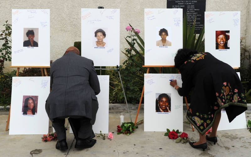 Reverend Dr. Kelvin Calloway (L) leaves a message on photographs set up as a memorial for 10 of the victims of the serial killer dubbed the Grim Sleeper.