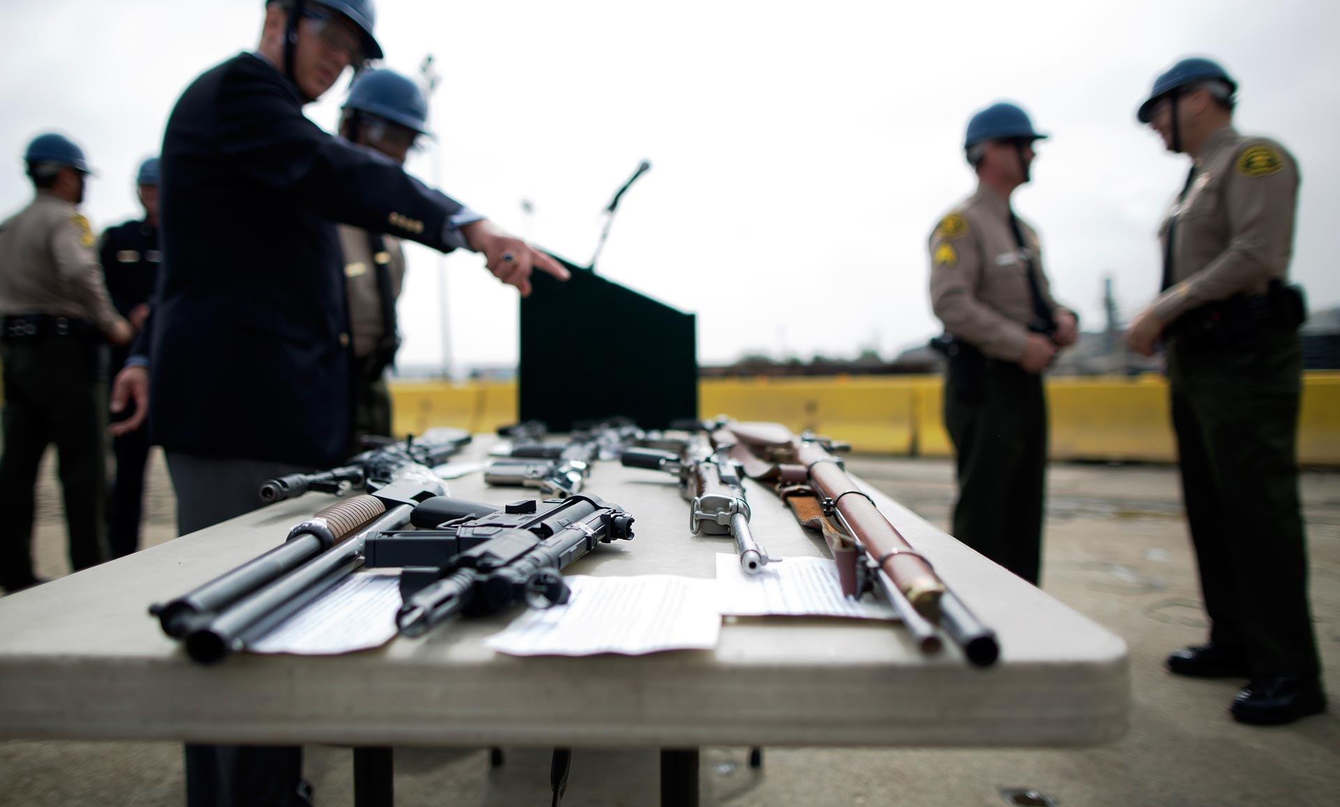 Officials look at guns confiscated in various law enforcement operations at a Los Angeles County Sheriffs' annual gun melt.