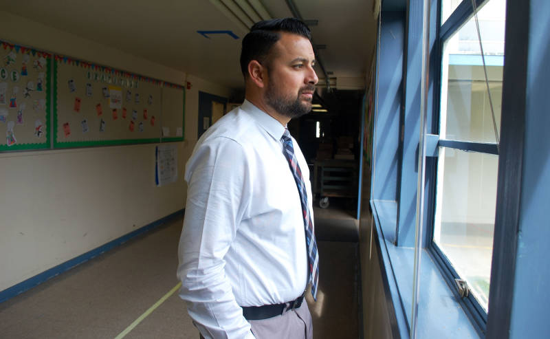 Oak Ridge Elementary School Principal Daniel Rolleri looks out a hallway window as he makes the rounds on campus. The school serves low-income families in a challenging neighborhood in Sacramento.
