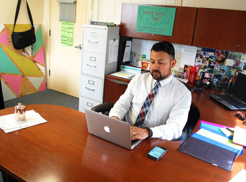 Principal Daniel Rolleri works from his desk on a typical school day morning. He's leading a campus which is facing some serious financial decisions despite getting additional revenue from the state.
