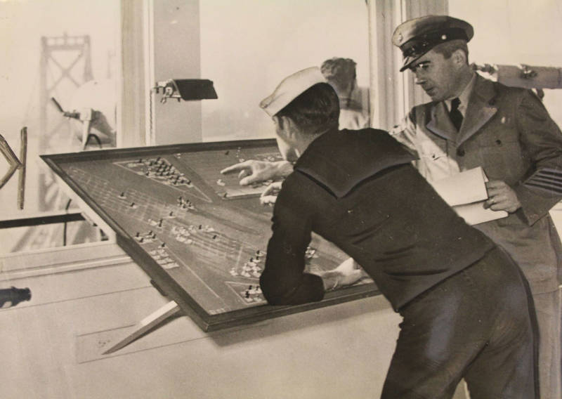 Navy signal corpsman F.R. English at the berth board receiving instruction from Chief Signalman Stanley Jones. The operations of the signal tower were military secrets until Dec 27th, 1945. One of the towers of the Bay Bridge's western span is visible in the background.