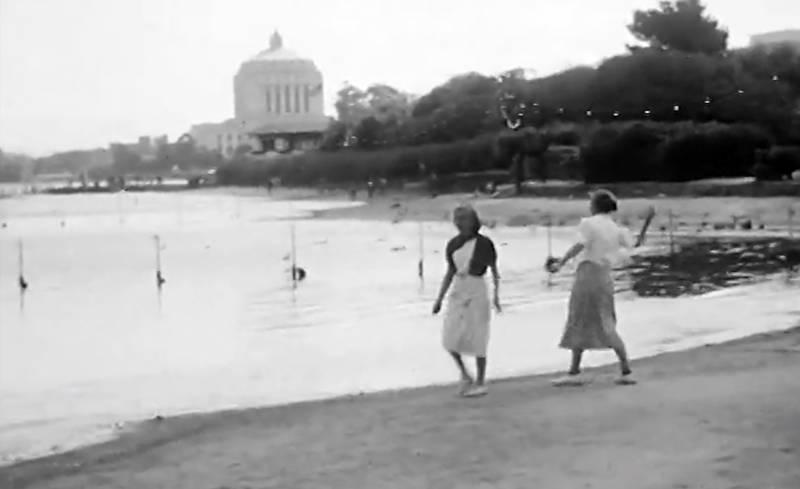 Ladies throwing rocks along the Lake Merritt waterfront.