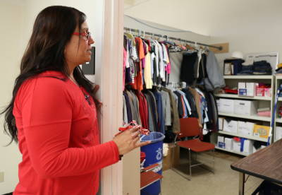 Martha Hurtado peeps her head in the HARTS program clothing donation closet which stores clothes, shoes and socks for students in the program.