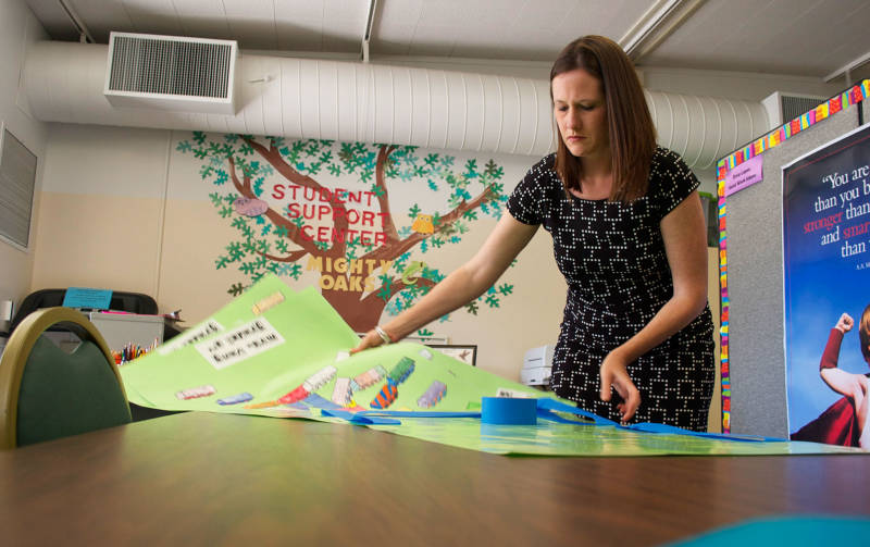 Bethany Coburn, a social worker and coordinator of the Student Support Center at Oak Ridge Elementary, prepares posters with inspirational messages written by students.