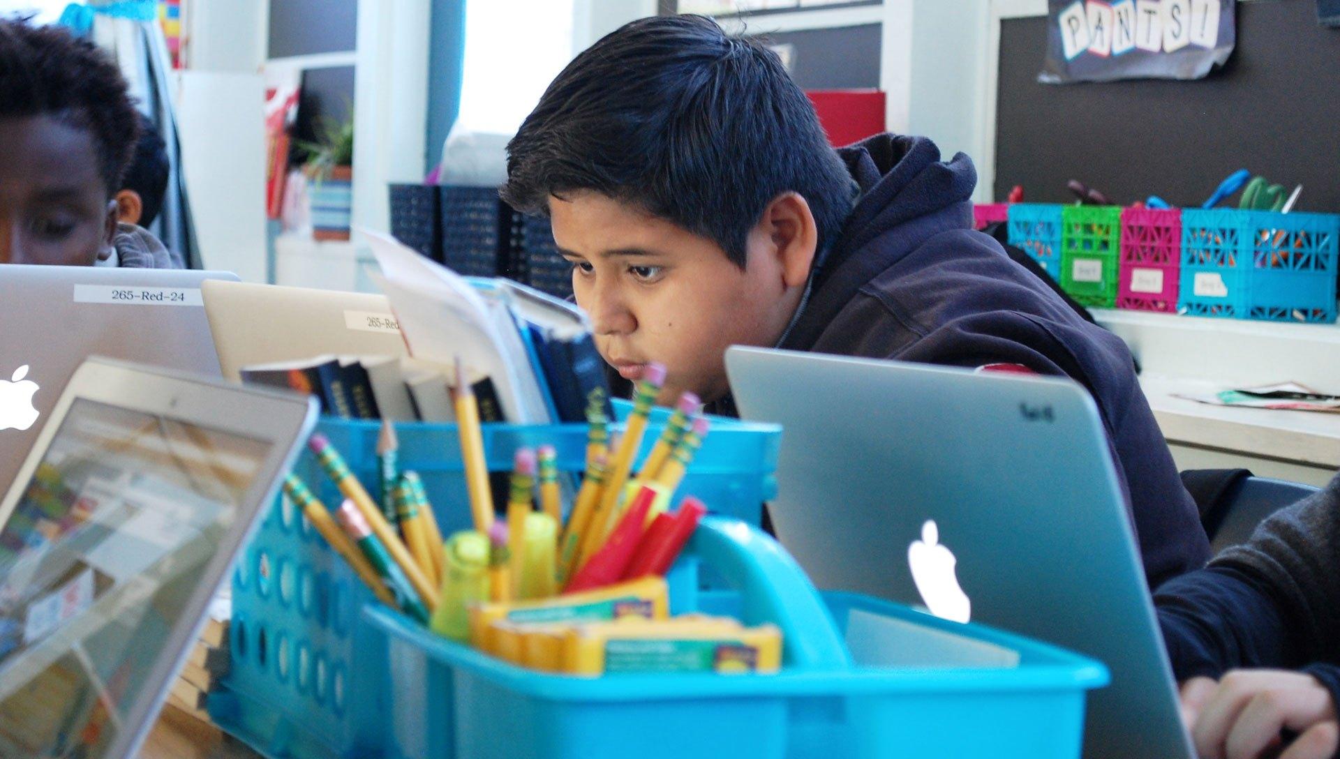 Carlos Delrio, de once años, se dedica a completar una asignación de computación en su clase de sexto grado en la escuela Oak Ridge Elementary en Sacramento.