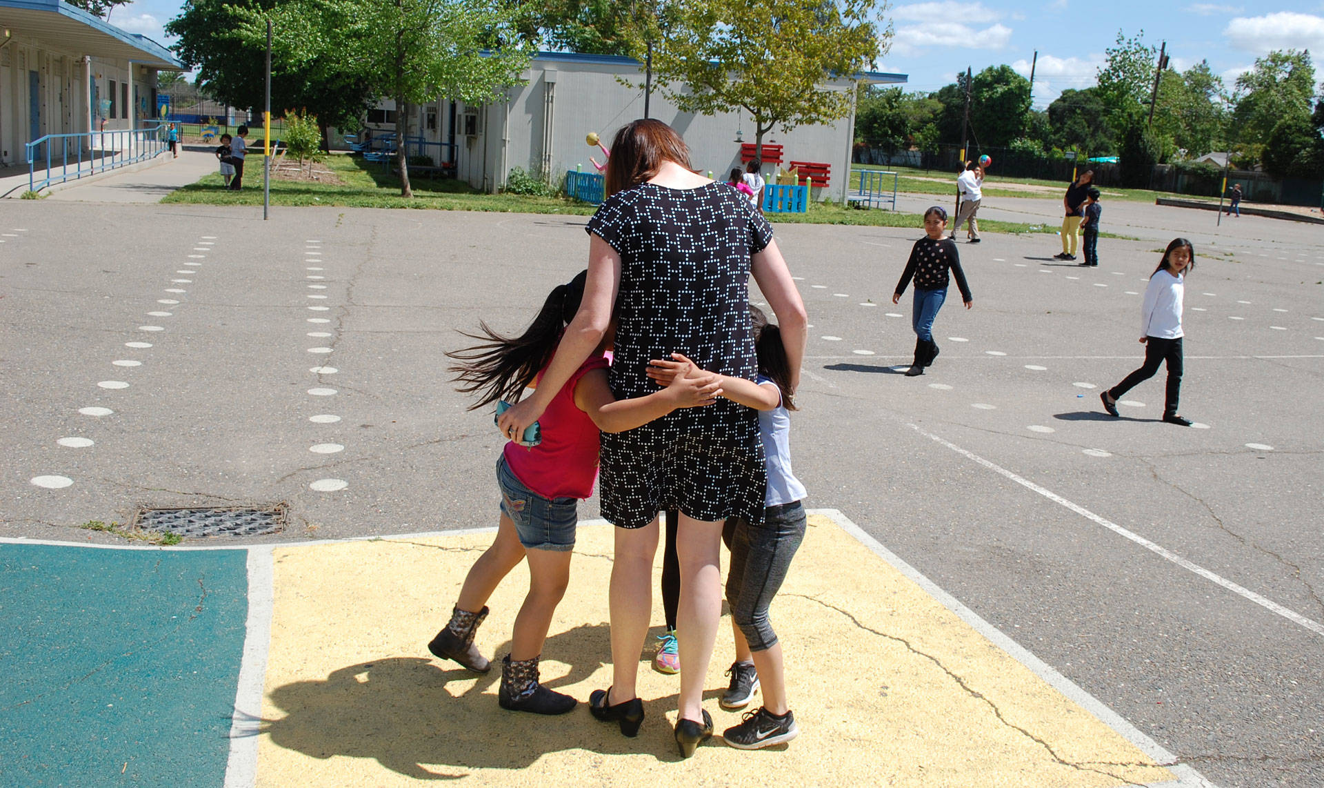 Bethany Coburn, a social worker and coordinator of the Student Support Center at Oak Ridge Elementary, receives a group hug from students on campus. Gabriel Salcedo/KQED