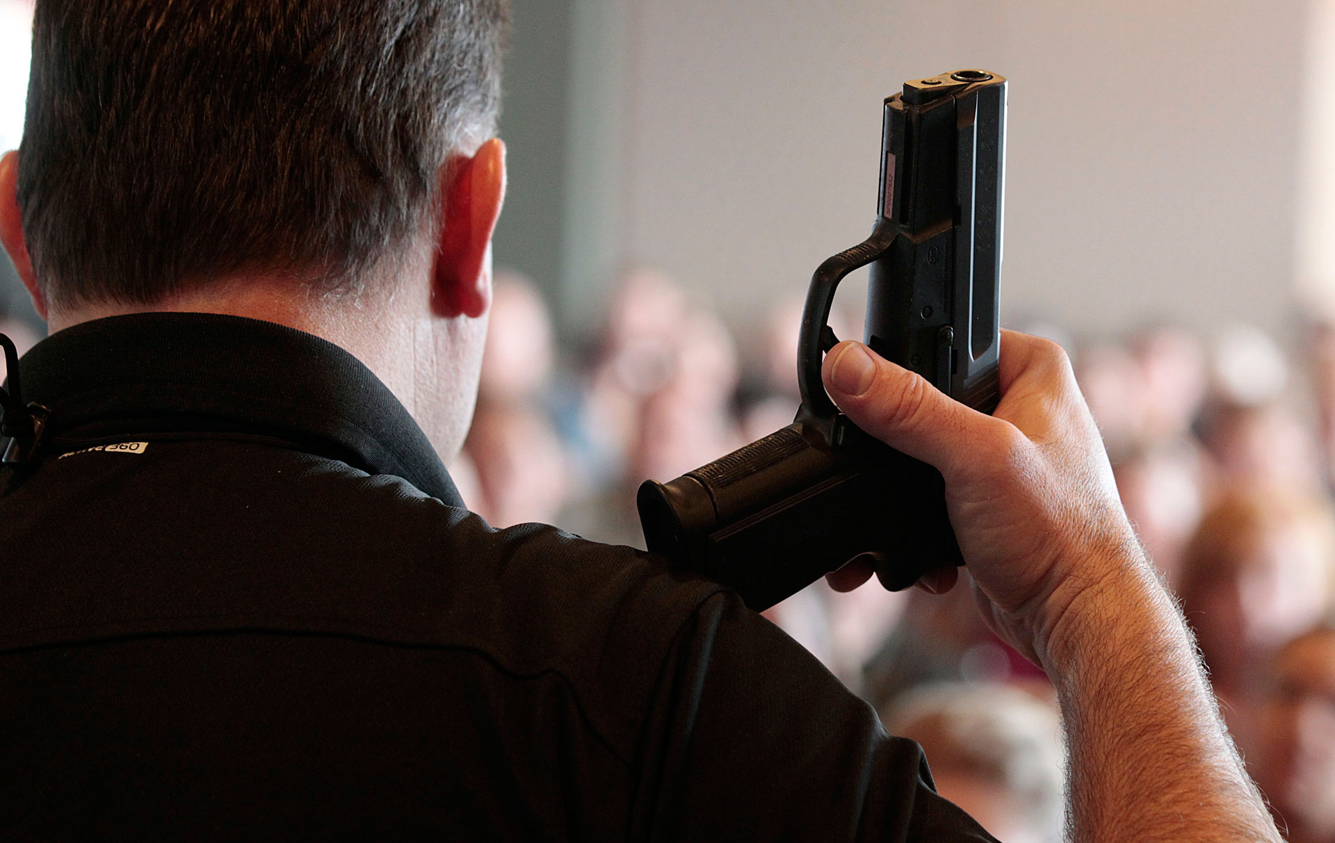 A firearm instructor holds a handgun up as he teaches a concealed-weapons training class to teachers in Utah.