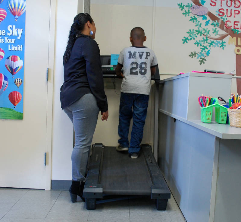Danielle Martin helps a student use a treadmill in Room 30 at Oak Ridge Elementary School. The treadmill is used on a daily basis for kids to release stress and refocus their energy.