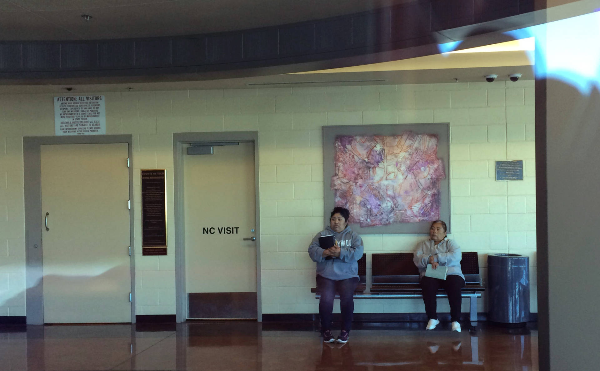 Pablo Aguilar's mother, Evelyn, and grandmother, Albertina, wait in the lobby of the Yolo County Juvenile Detention Facility to visit Pablo, who has been locked in confinement by the Office of Refugee Resettlement since June of 2014. Tyche Hendricks/KQED