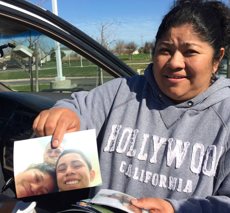 Evelyn holds up a photo of herself visiting with her son Pablo when he was detained at a facility in Oregon in 2015. Her friend Mario is in the background of the photo.