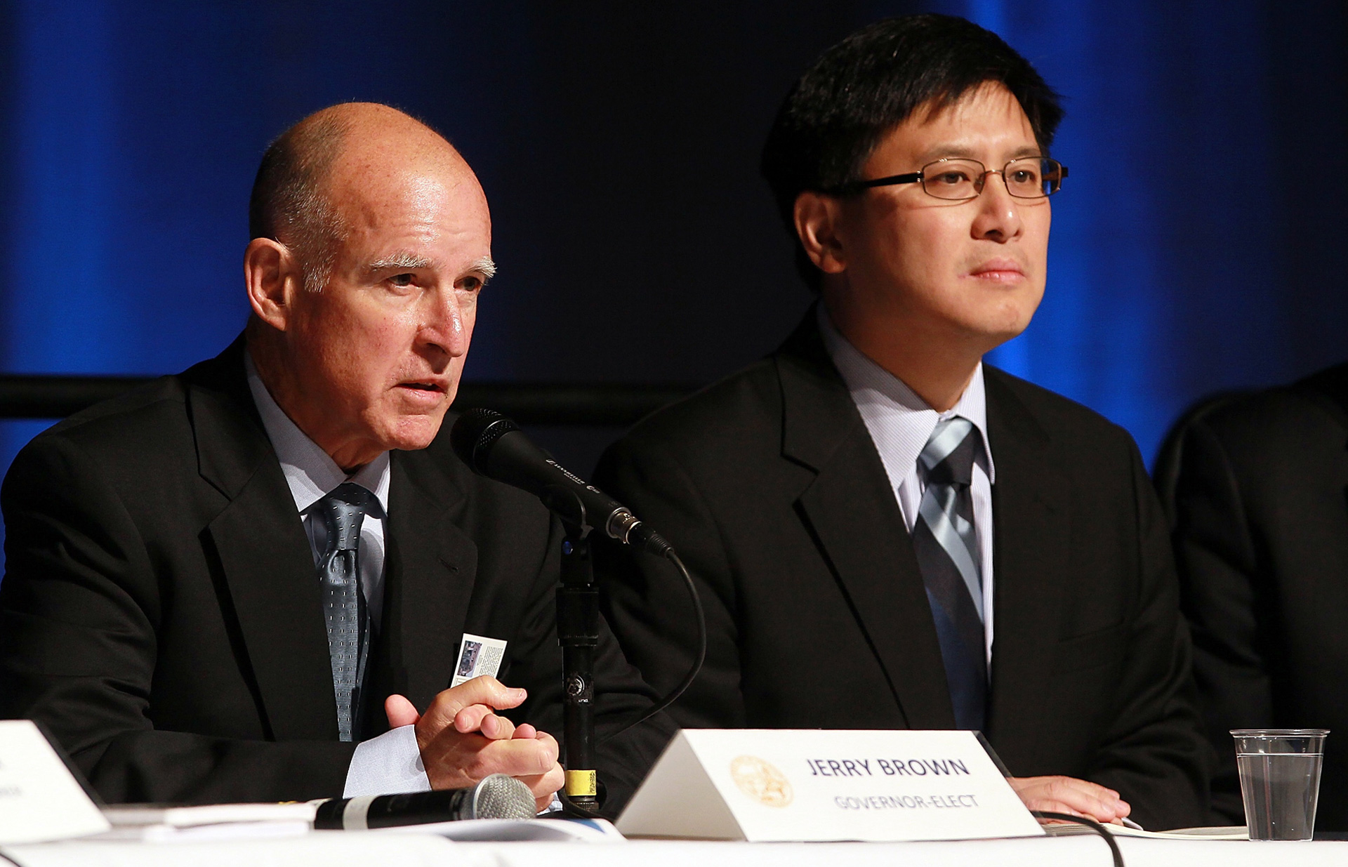John Chiang looks on as then governor-elect Jerry Brown speaks during a state budget briefing on December 8, 2010.