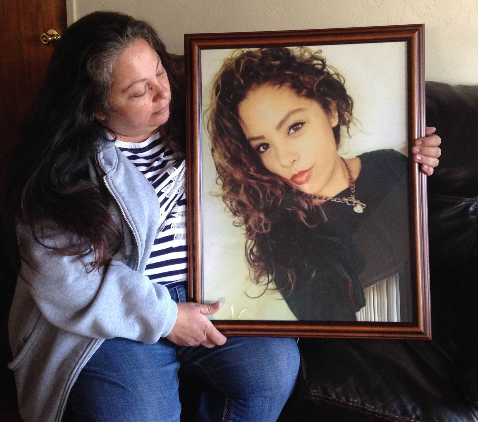 Maria Spivey, a bus driver in San Diego, looks at a photo of her daughter, Chloe Roston.