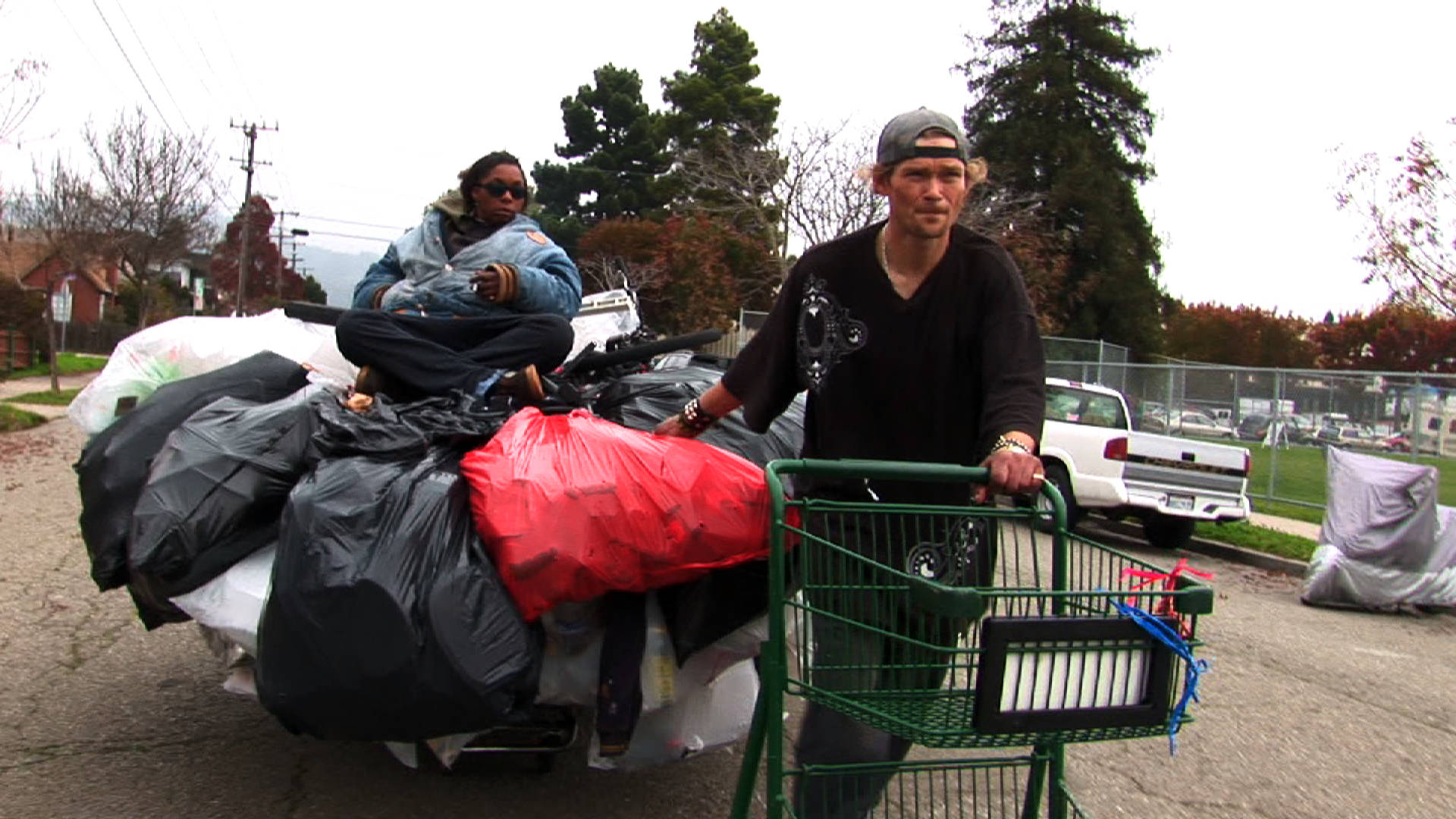 Jason Witt (right), the Olympic champion of recycling, hauls a shopping cart with his girlfriend, Heather Holloman (left), on top.