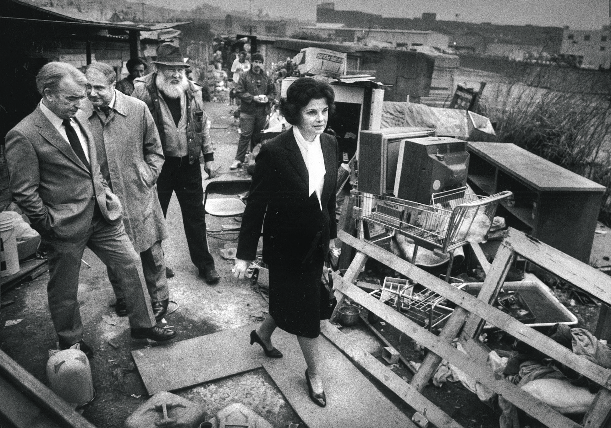 Mayor Dianne Feinstein and members of her administration walk through a shantytown slated for dismantling near Seventh and Berry streets.