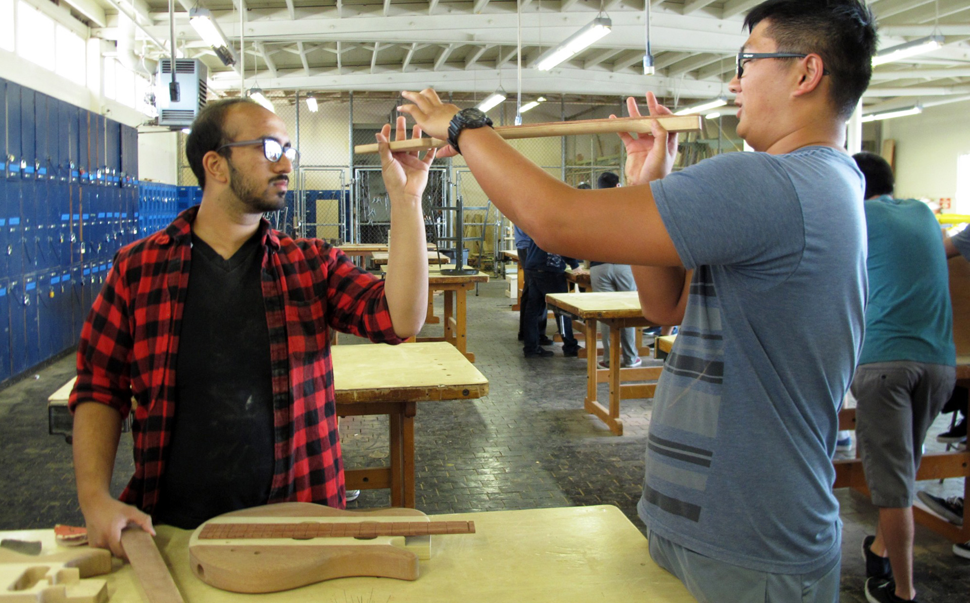 Senior Timothy Lee (R) checks out the curve on his fretboard with help from classmate Farhan Saleh. The two are taking wood shop and physics at Camarillo High School as part of the STEM Guitar Project.