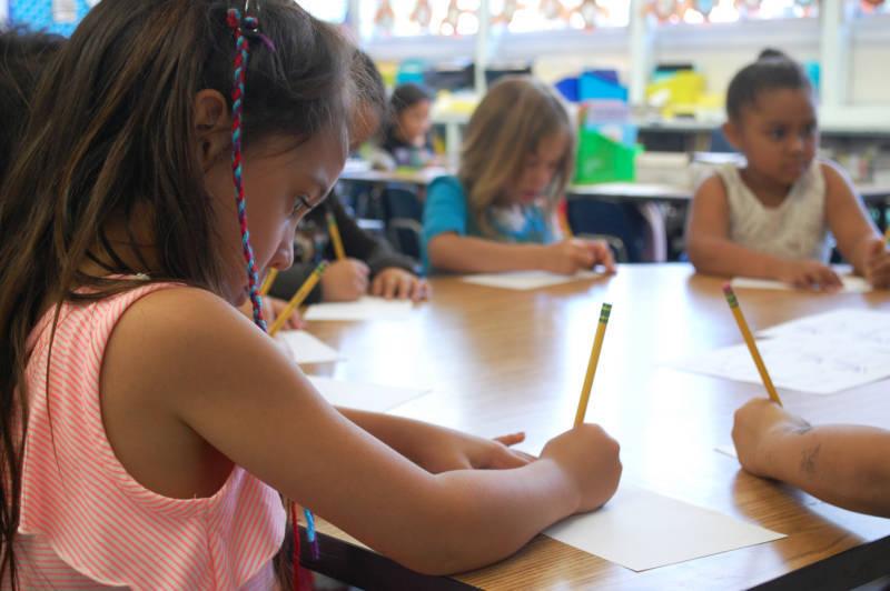 Una estudiante de kinder de la escuela primaria de Oak Ridge completa una lección de redacción para perfeccionar sus habilidades lingüísticas.