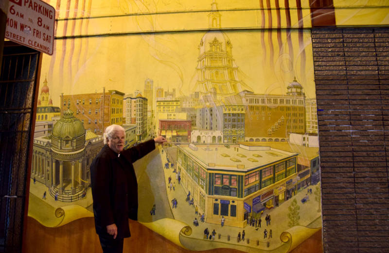 Minister Lyle Beckman points out where we are on an intricate mural depicting the ghosts of churches leaving the Tenderloin. With them often go services rendered to the poor and homeless in the area.