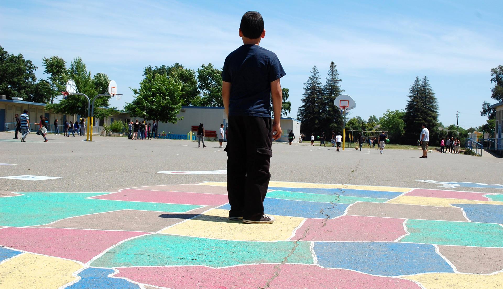 Caption: Arriba: Más de 500 estudiantes asisten a la Oak Ridge Elementary School en Sacramento. Muchos hablan el inglés como segundo idioma. Bajo la nueva manera de distribuir fondos del estado, las escuelas con altos números de tales estudiantes ahora reciben fondos adicionales para ayudar a acelerar los logros académicos.