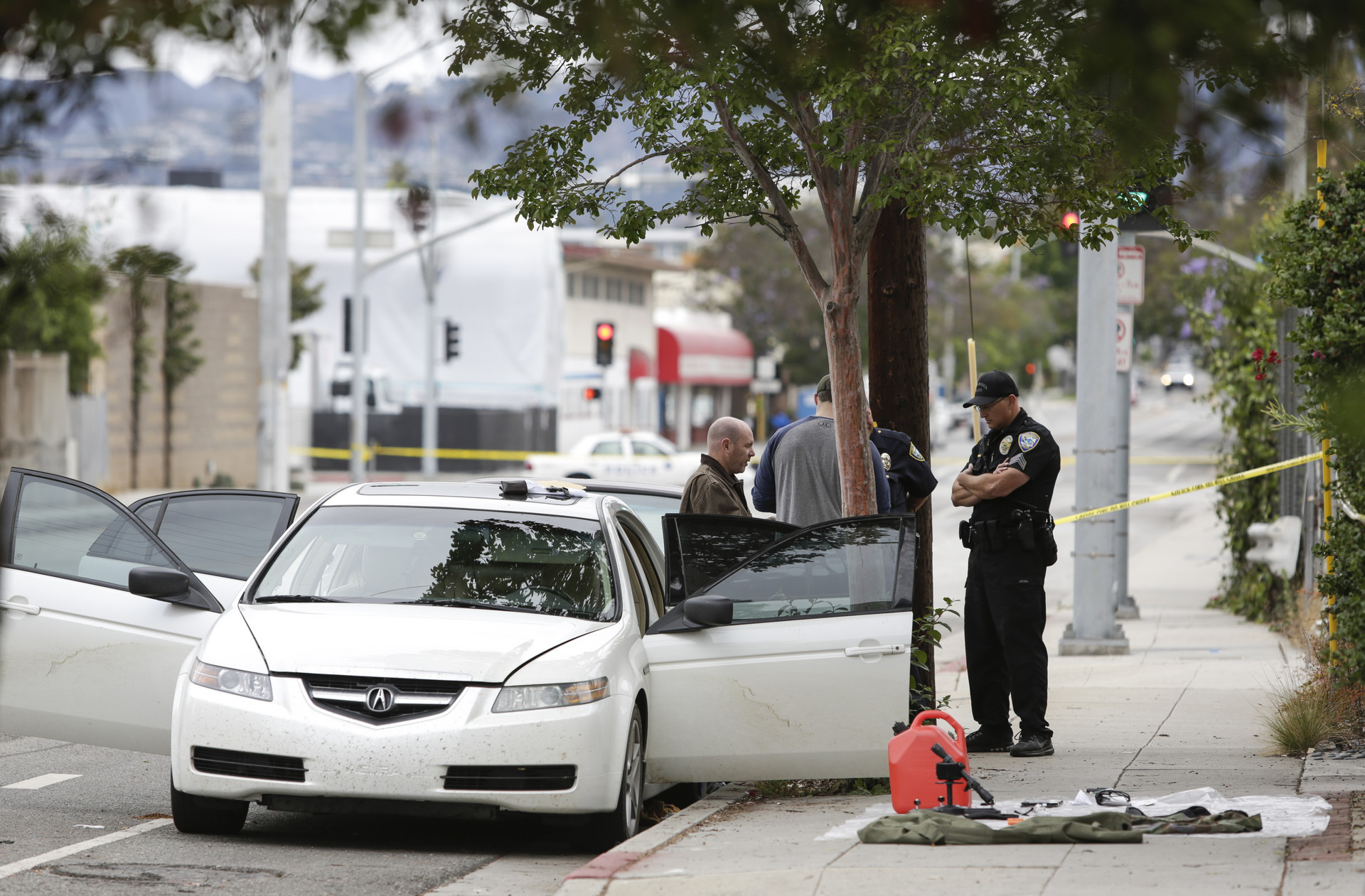 Police investigate a white sedan in Santa Monica on June 12, 2016. In the car, they found three assault rifles, high-capacity magazines and ammunition and a chemicals that could be used to make an explosive device.