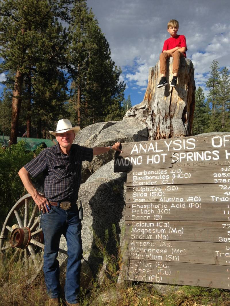 Jeff Winslow stands by a sign that tells what minerals are in the springs. Asher Boone sits on a rock above.