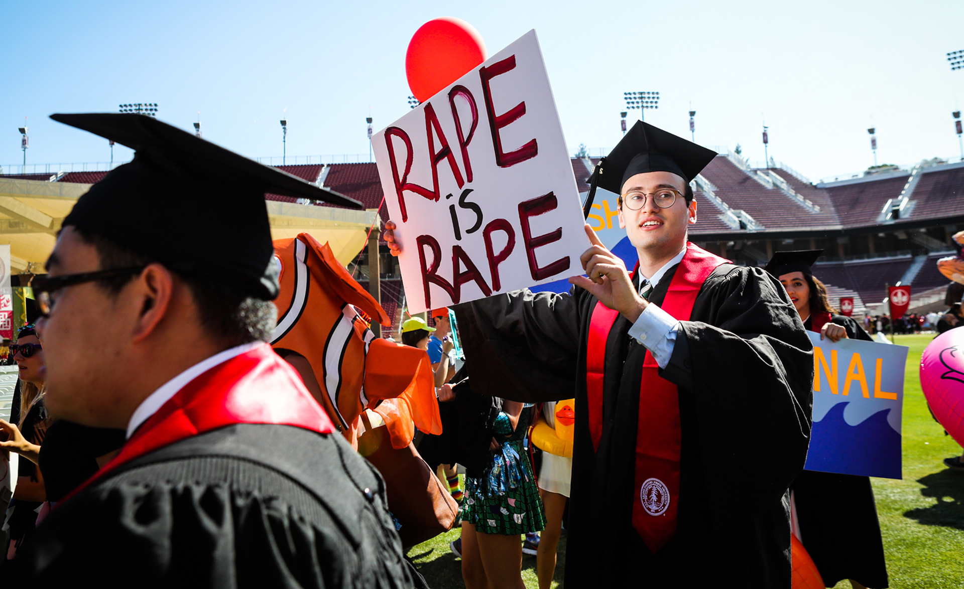 Stanford student Paul Harrison carries a sign in a show of solidarity for the victim in the Brock Turner case during graduation ceremonies at Stanford University on June 12, 2016.
