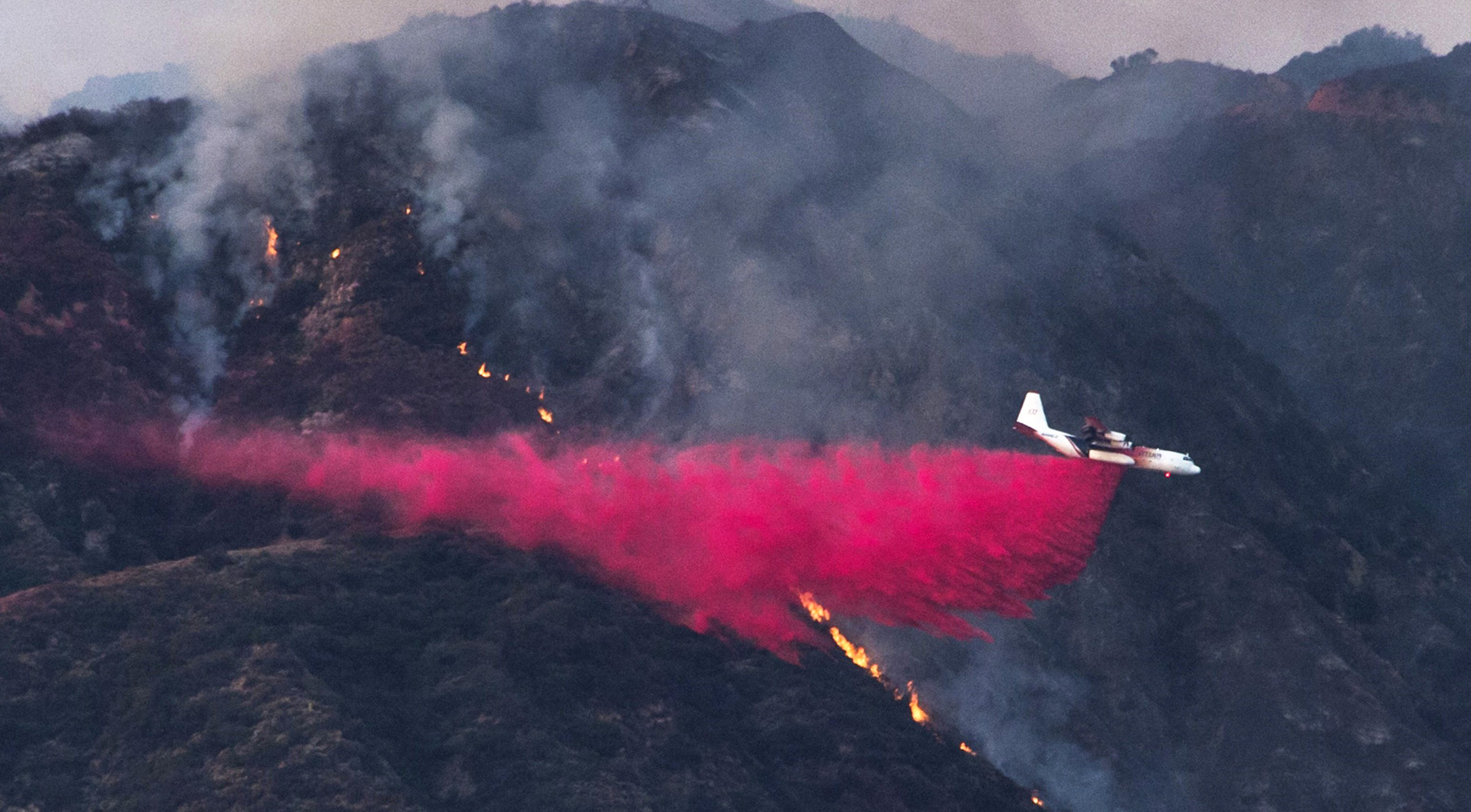 An aircraft drops fire retardant to prevent the advance of the San Gabriel Complex Fire in the Angeles National Forest, near Duarte on June 21, 2016.