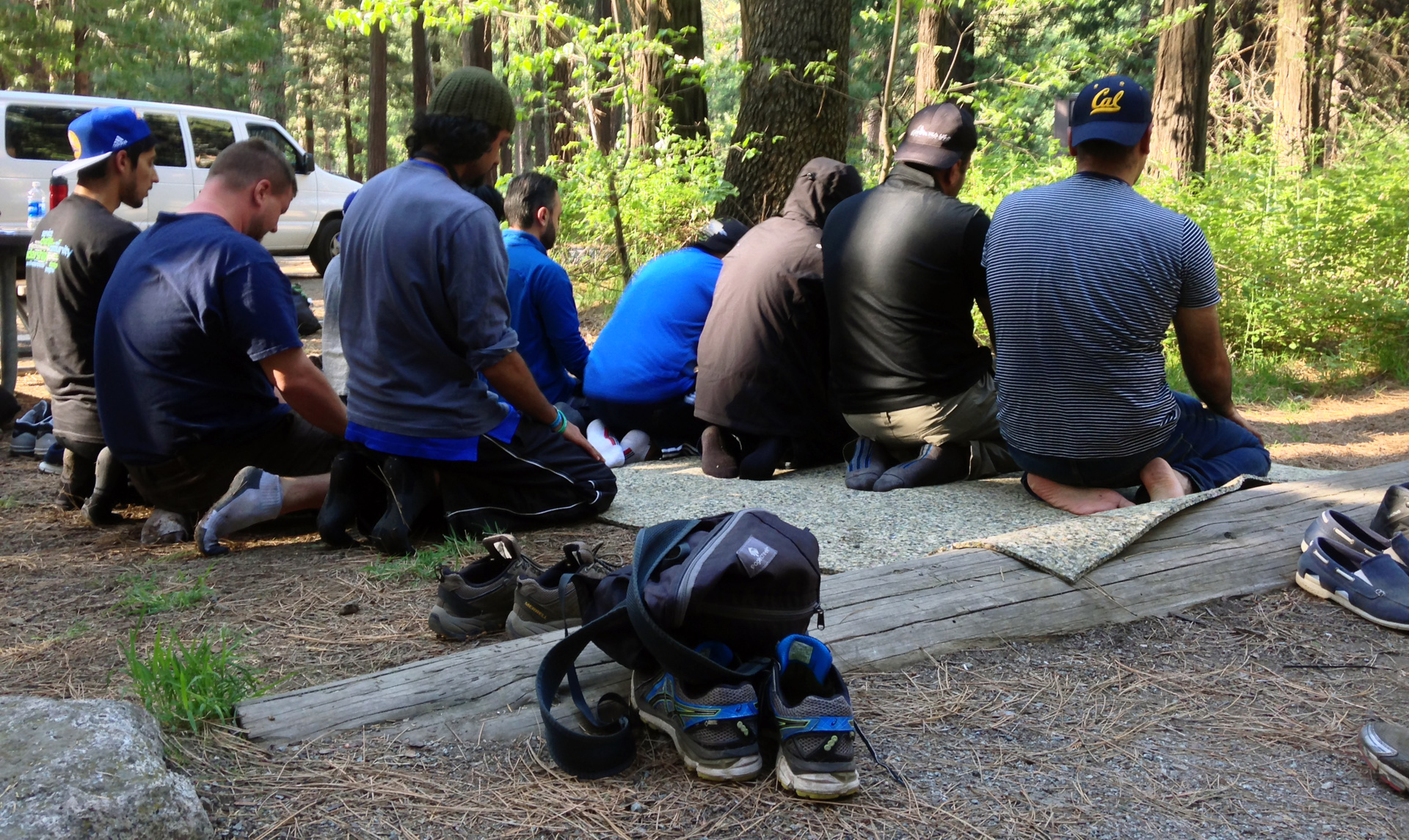 Young Muslim men pray at a campsite in Yosemite.