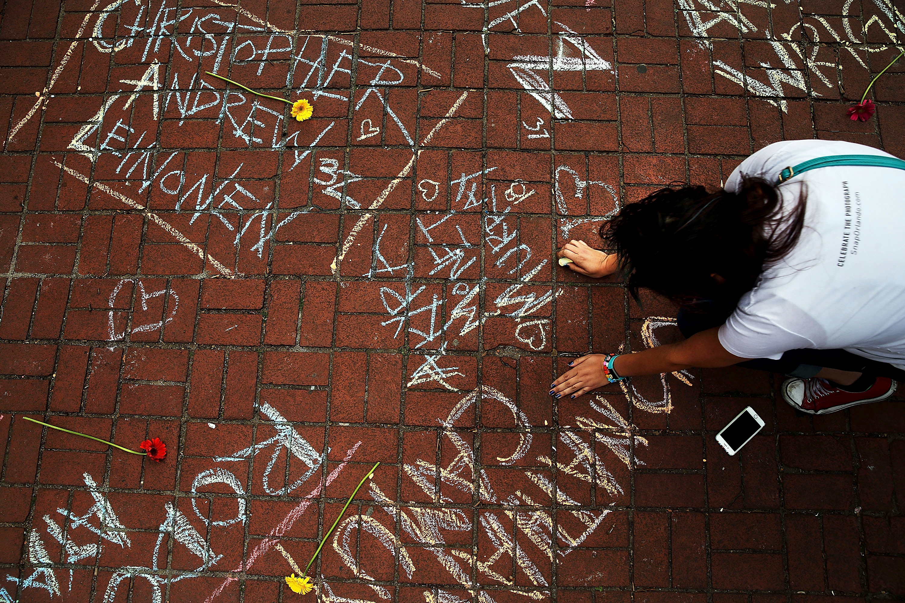 A woman pauses while writing the names of shooting victims in chalk in a park across from the iconic New York City gay and lesbian bar, The Stonewall Inn, on June 13, 2016 in New York City.