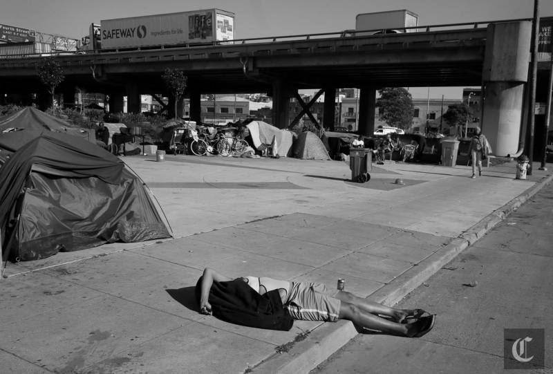 A homeless woman from the encampment on 5th Street near the Bay Bridge entrance laid in the sidewalk and street Tuesday March 3, 2015. Homeless encampments are still prevalent in San Francisco, Calif. and their locations are becoming more apparent.