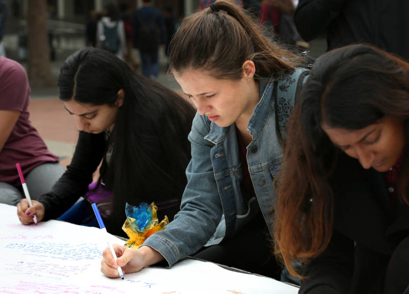 Tarishi Jain's roommate, Hannah Rowe, writes a message to Jain on a banner during a vigil for the 19-year-old UC Berkeley student, one of the victims of an attack at a Dhaka cafe in Bangladesh on July 2,2016. The vigil was held on UC Berkeley's campus in Berkeley, Calif. on July 5, 2016.