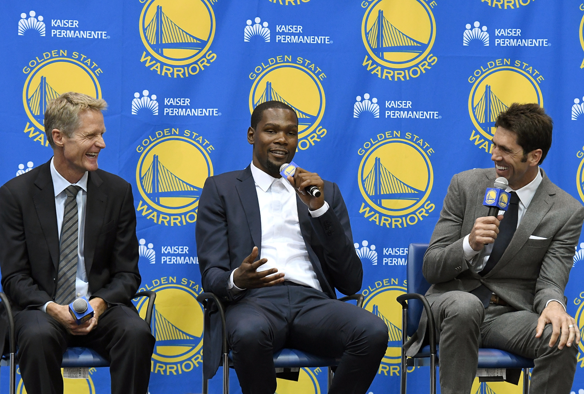 Head coach Steve Kerr of the Golden State Warriors sits with Kevin Durant and general manager Bob Myers.