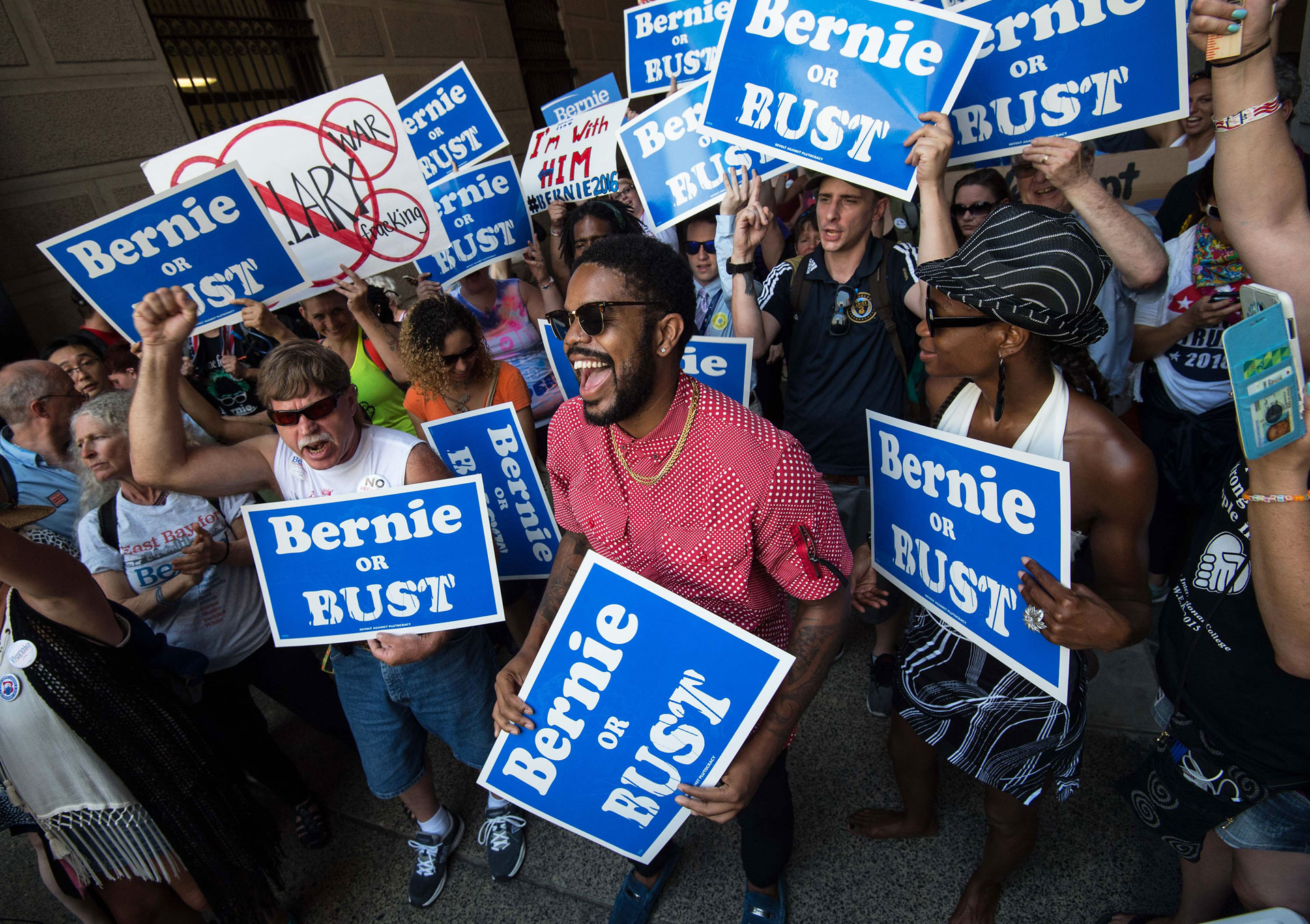Supporters of Bernie Sanders hold signs at a rally at City Hall in Philadelphia on July 25, 2016,