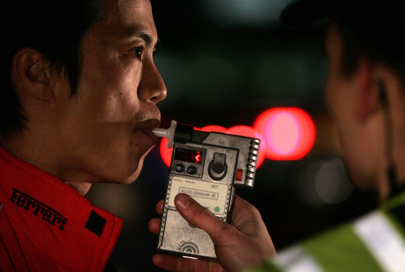 A man blows into a breathalyzer during a field sobriety test for alcohol. A scientifically sound field sobriety test for marijuana is much trickier to design.