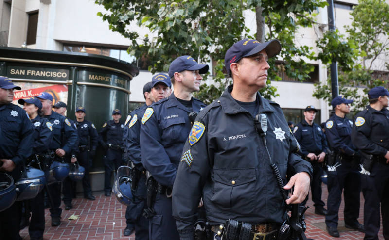 """A San Francisco Police Officer looks on as protestors chant: """"These racist cops have got to go."""""""