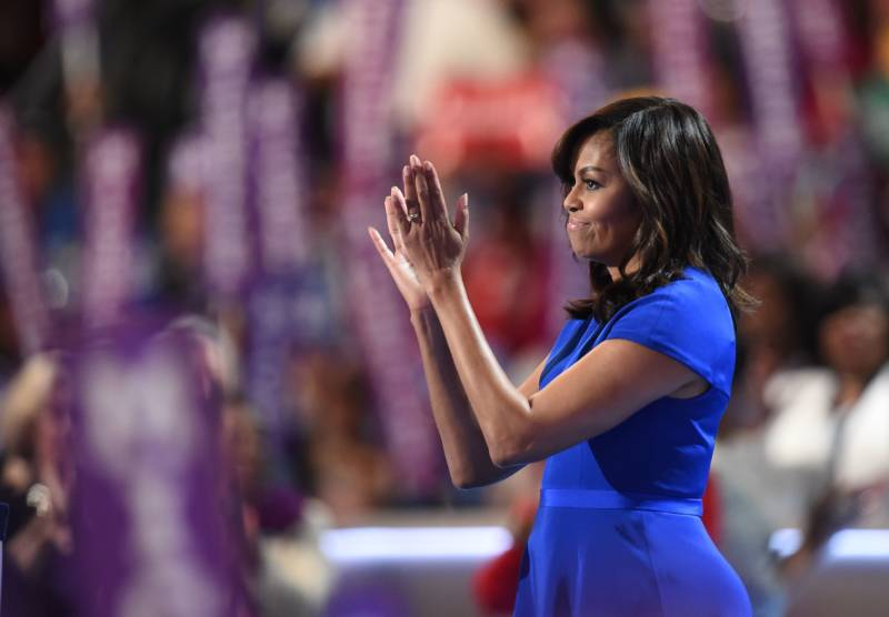 First Lady Michelle Obama applauds from the stage after addressing delegates on the first day of the Democratic National Convention in Philadelphia.