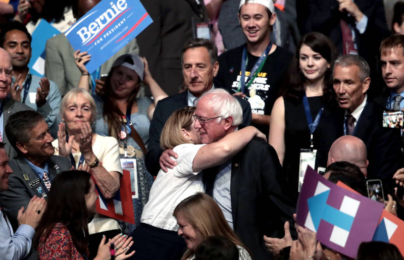Sen. Bernie Sanders hugs an attendee during roll call on the second day of the Democratic National Convention.