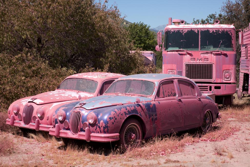 Pink fire retardant covers cars near Ryan Nuckols' home as the Pilot Fire burns nearby in Hesperia, California.