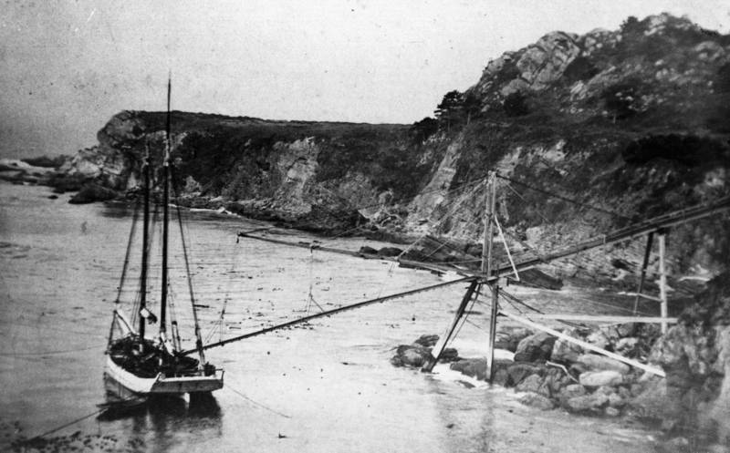 A waiting schooner at a Timber Cove doghole port is moored at three points, perilously close to shore, to receive its cargo.