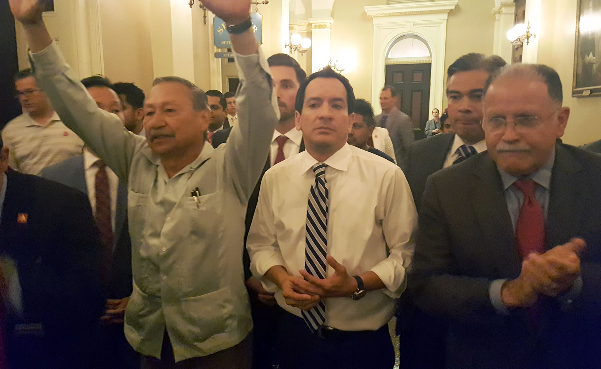 United Farmworkers President Arturo Rodriguez (L, arms raised) and Assembly Speaker Anthony Rendon (C) emerge after meeting about AB 1066 on Thursday, August 25, 2016.