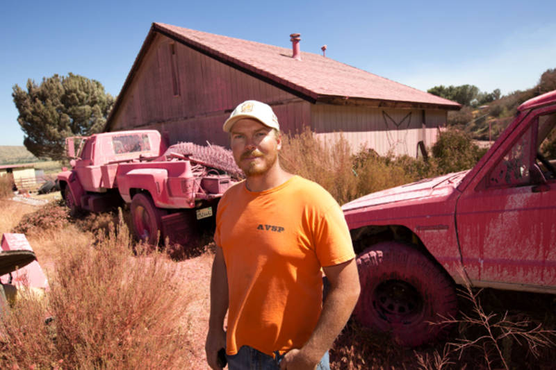 Hesperia resident Ryan Nuckols on his property. Fire crews doused his home with pink fire retardant in attempt to keep it safe.