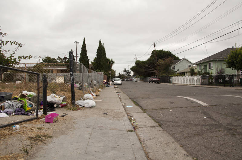 Abandoned trash sits along the sidewalk and in an empty lot on 105th Avenue in the Madison Park neighborhood in Oakland on Aug. 26, 2016.