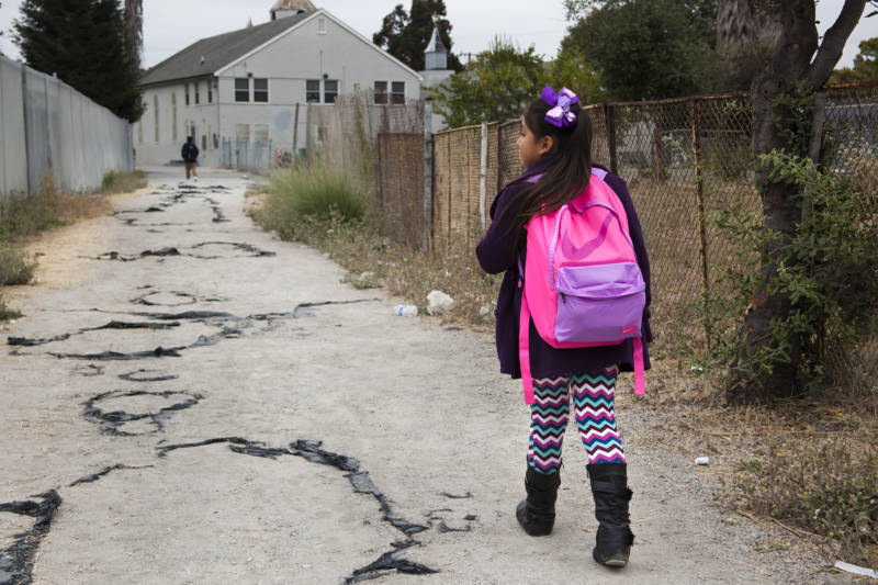 Seven-year-old Celia Fragoso walks through her neighborhood in Madison Park in the morning on her way to Sobrante Park Elementary in Oakland on Aug. 26, 2016.