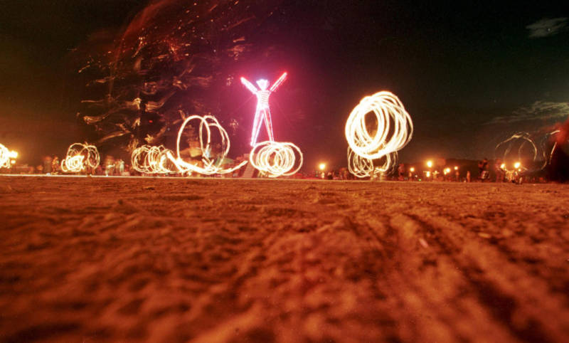 Dancers at 1998's Burning Man festival create patterns with fireworks.