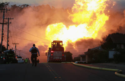 A law enforcement official runs towards a massive fire in a residential neighborhood September 9, 2010 in San Bruno, California.
