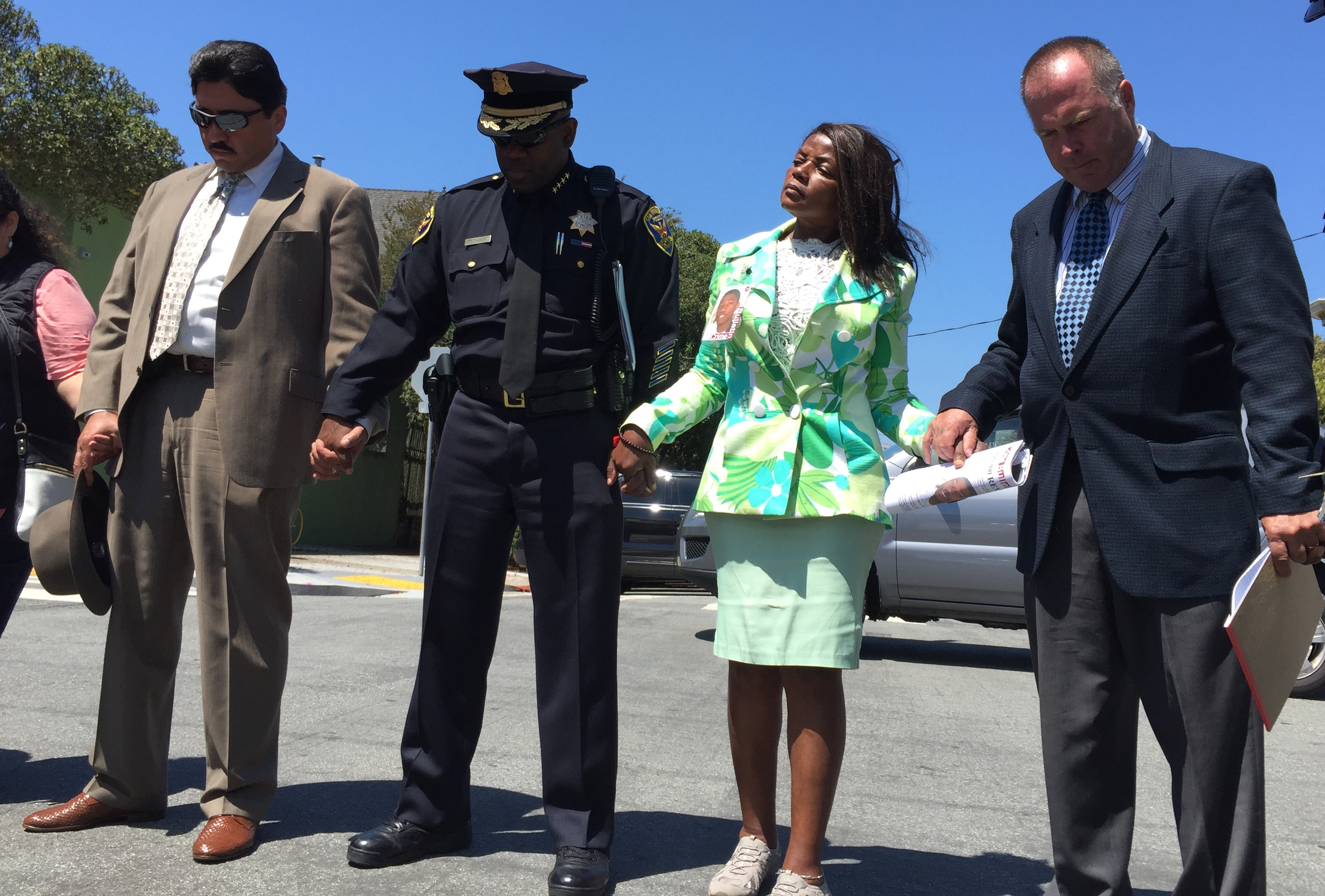 SFPD Homicide Inspector Gianrico Pierucci, Chief Toney Chaplin, Paulette Brown and Inspector Jim Spillane pray on Aug. 12, 2016, at the scene where Aubrey Abrakasa Jr. Was shot dead approximately 10 years ago.