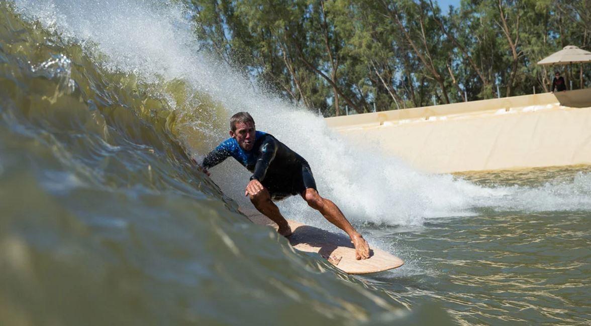 A surfer rides a longboard at the secret wave spot.