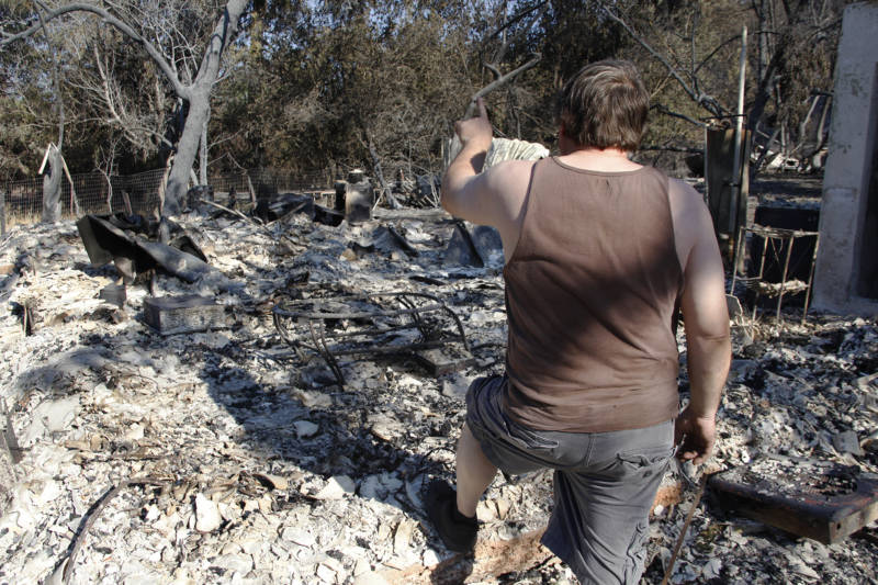 Michael Skidmore points out where certain rooms use to be in his family's home before the Clayton fire in Lower Lake, California destroyed it.