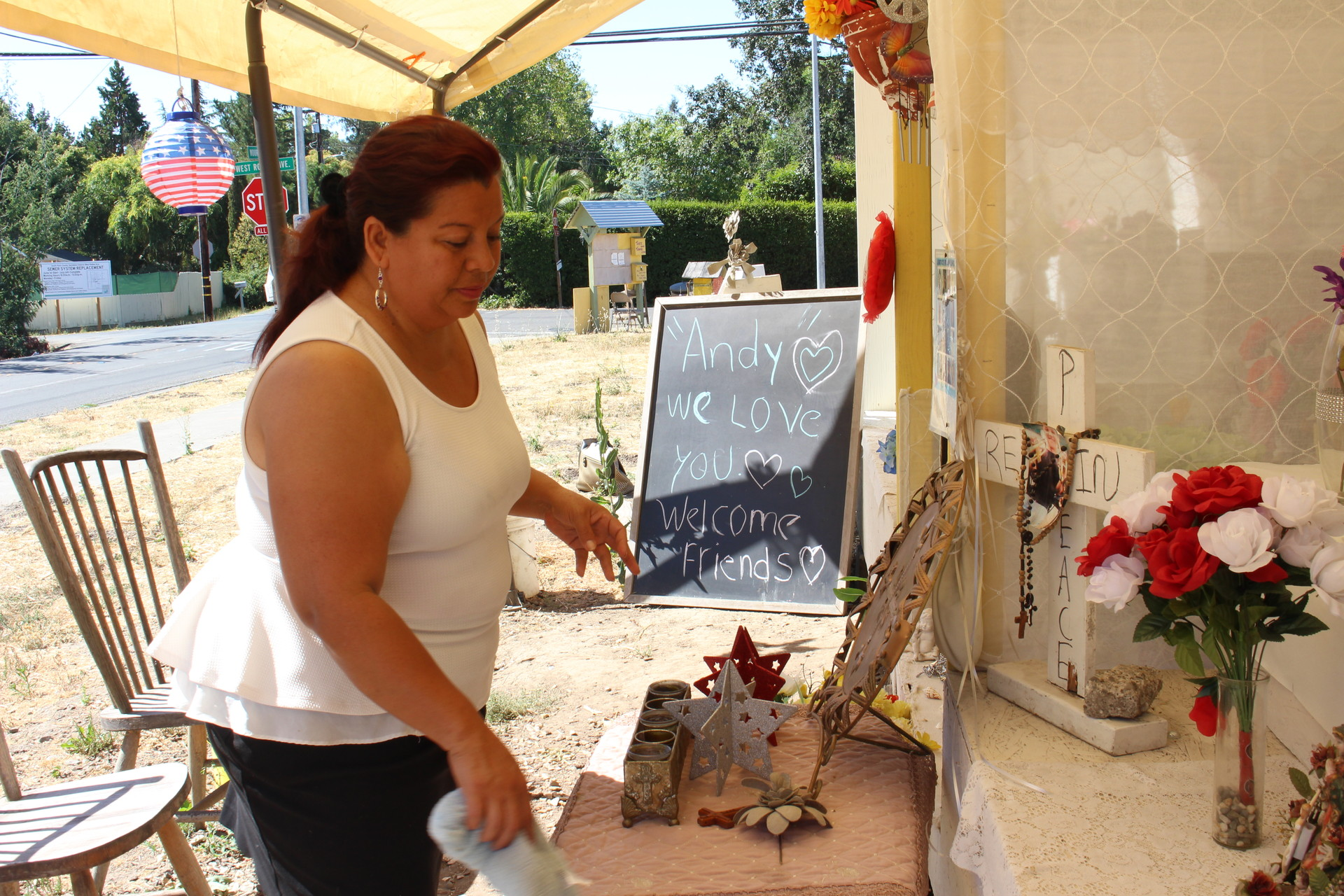"""Concepcion Dominguez cleans a memorial for Andy Lopez on July 26, 2016 at the site of his death on a lot he used to play in. Dominguez, a former neighbor of Lopez's, says she would prefer Gelhaus be kept off street patrol. """"It's too dangerous"""" for residents,"""