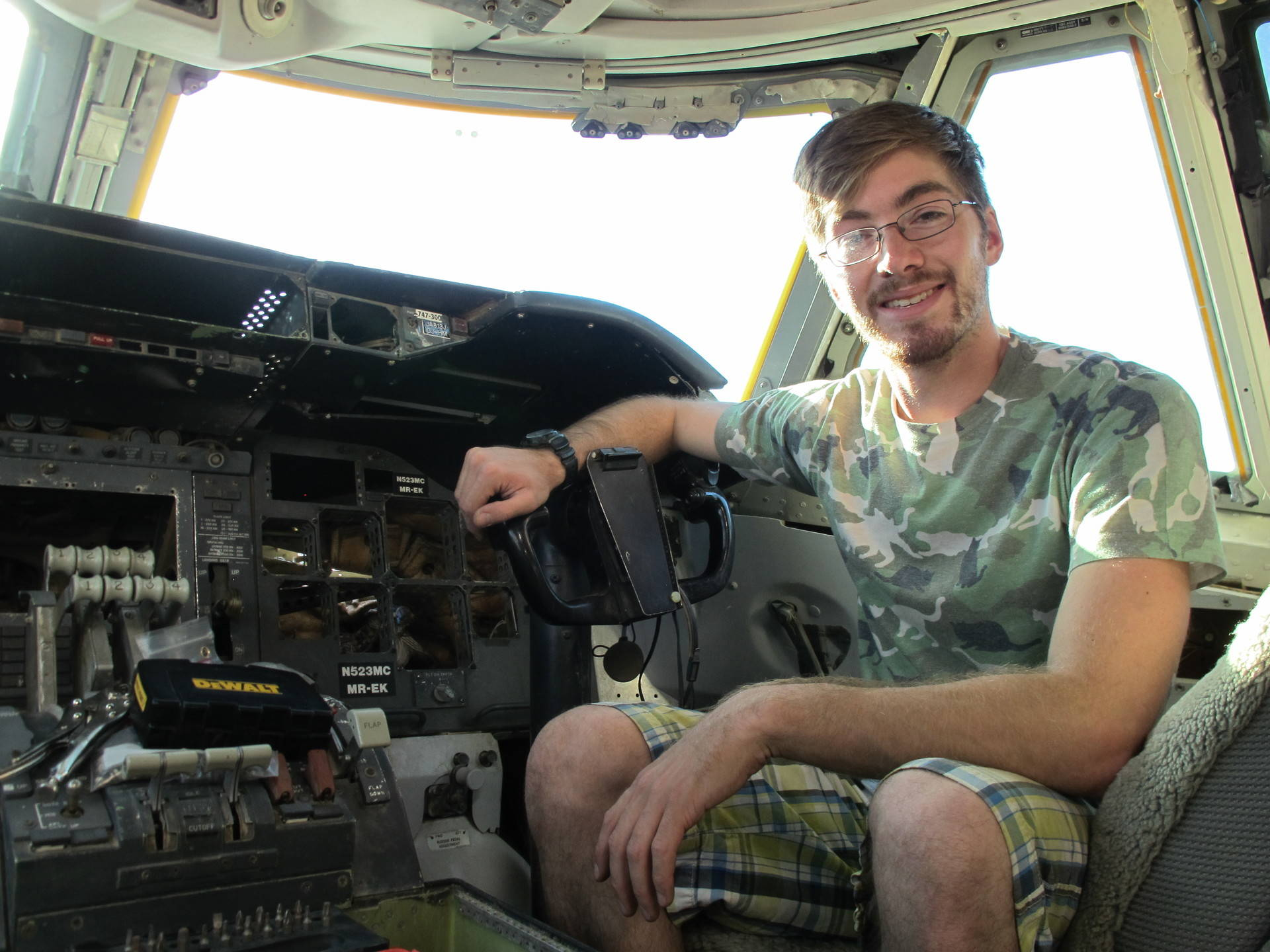Volunteer Nick Avila of San Francisco sits in the 747 cockpit that he's helping to fix up for Burning Man. Susan Valot/KQED