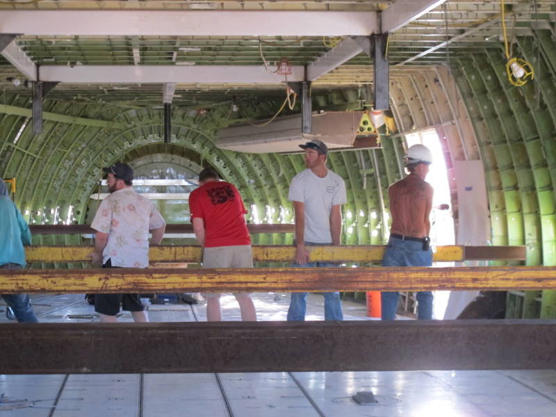 747 Project creator Ken Feldman (Hawaiian shirt), workers and volunteers help place beams that will help transport the plane to Burning Man.